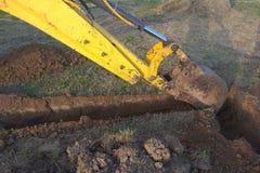 Ein Arbeitsbagger gräbt einen Graben in einem Landhaus lizenzfreie stockfotografie