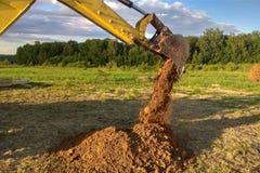 Ein Arbeitsbagger gräbt einen Graben in einem Landhaus stockbilder