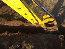 Ein Arbeitsbagger gräbt einen Graben in einem Landhaus lizenzfreies stockbild
