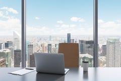 Ein Arbeitsplatz in einem modernen panoramischen Büro mit New- Yorkansicht Eine graue Tabelle, brauner Lederstuhl Stockfotos