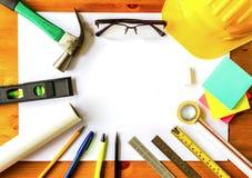 Ein Architektenarbeitsschreibtisch mit Werkzeugen und Schutzhelm mit Kopienraum stockbilder
