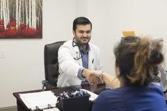 Ein Arzt, der an einem Schreibtisch sitzt stockfoto