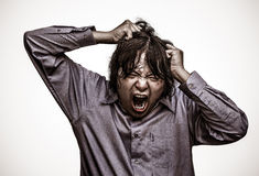 Ein asiatischer Bürokerl betont zu seiner Grenze in schwerem Korn gru Stockfotos