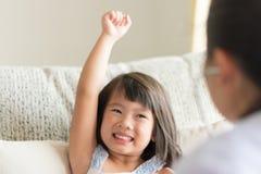 Ein asiatischer Blick des kleinen Mädchens überzeugt wenn Doktor, der durch u überprüft stockbilder