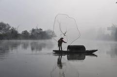 Ein asiatischer Fischer mit traditionellem und altem Fischernetz und Boot arbeitet im Morgennebel Lizenzfreie Stockfotografie