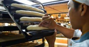Ein asiatischer Mann, der Brot an der Bäckerei macht stockfotografie