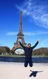 Ein asiatischer Mann, der vor Eiffelturm springt Stockfoto