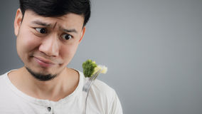 Ein asiatischer Mann isst Brokkoli Lizenzfreie Stockfotos