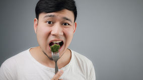 Ein asiatischer Mann isst Brokkoli Stockbild