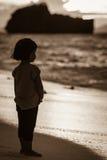 Ein asiatisches kleines Mädchen, das allein auf dem Strand steht Stockbild
