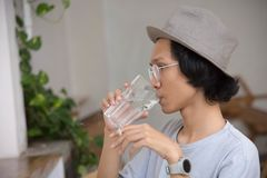 Ein asiatisches Manngebrauchshut- und -glasrauchen und Trinkglas Wasser am Café stockbild