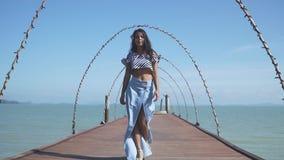 Ein asiatisches Modell in einem blauen Kleid geht auf einen Pier wie auf dem Podium stock footage