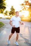 Ein Athlet in einem weißen T-Shirt und einem Läufer der kurzen Hosen am Abend, rüttelnd Ein Mann im Park hört auf ein audiobook,  Lizenzfreie Stockbilder