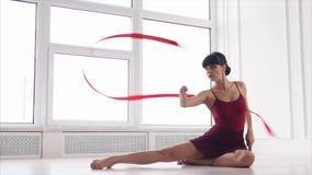 Ein Athlet mit Tätowierungen auf ihrem Körper führt die künstlerischen Elemente durch, die auf Boden sitzen stock video footage