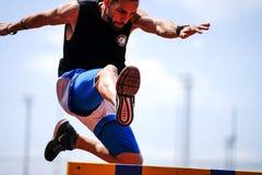 Ein Athlet springt über eine Hürde während des Übens auf einer Laufbahn stockfoto