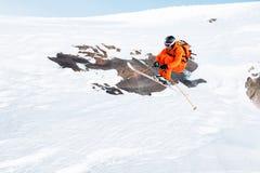 Ein Athletenskifahrer springt vom hohen Felsen hoch in den Bergen stockfotografie