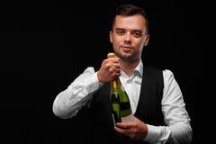 Ein attraktiver Barmixer öffnet eine Flasche Champagner, Getränke für Parteien auf einem schwarzen Hintergrund lizenzfreies stockbild