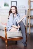 Ein attraktiver flirty junger Brunette liegt in einem großen weichen Stuhl Lizenzfreie Stockbilder