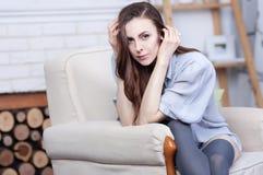 Ein attraktiver flirty junger Brunette sitzt in einem großen weichen Stuhl Lizenzfreie Stockfotos