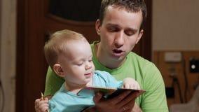 Ein attraktiver Junge 2 Jahre alt und Vater las ein Buch zu Hause Vati stellt dar, dass die Bilder und der Sohn die Tiere nennt stock video