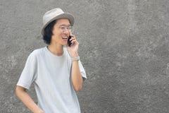 Ein attraktiver junger asiatischer Mann mit Hut und Gläsern unter Verwendung des smarphone stockbild