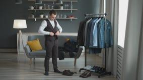 Ein attraktiver Mann denkt, um unterschiedliche Kleidung in einer Umkleidekabine f?r ein Gesch?ftstreffen oder ein Datum an zu kl stock video