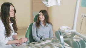 Ein attraktives junges Mädchen kam zur Aufnahme zu ihrem Zahnarzt und lächelte und gefiel mit dem Ergebnis der zahnmedizinischen  stock video