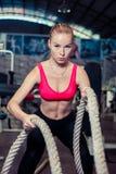 Ein attraktives junges und athletisches Mädchen, das Training verwendet, fängt eine Turnhalle ein Stockbild