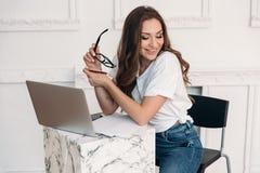 Ein attraktives Mädchen arbeitet an ihrem Projekt in einem gemütlichen Café und sitzt an einem Tisch, der durch einen Laptop, Aus stockfotografie