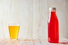 Ein Auffrischungsbeerengetränk in einer Plastikflasche mit einem vollen Glas hellem Bier im Hintergrund Kopieren Sie Platz Gesund lizenzfreies stockfoto