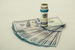 Ein aufgerollter 100 Dollarschein, der auf anderen stillsteht, angelte den 100 Dollarschein, der auf weißem Hintergrund lokalisie Stockfoto