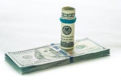 Ein aufgerollter 100 Dollarschein, der auf anderen stillsteht, angelte den 100 Dollarschein, der auf weißem Hintergrund lokalisie Lizenzfreie Stockbilder