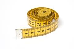 Ein aufgerolltes gelbes messendes Band Lizenzfreie Stockbilder