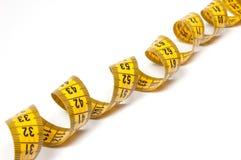 Ein aufgerolltes gelbes messendes Band Stockfotos