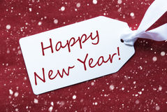 Ein Aufkleber auf rotem Hintergrund, Schneeflocken, Text-guten Rutsch ins Neue Jahr Stockbilder