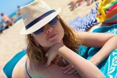 Ein Aufstellungsmädchen, das auf einen Strand legt Stockfoto
