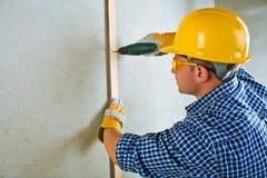 Ein Auftragnehmer, der mit elektrischem screwdriwer arbeitet Lizenzfreie Stockbilder