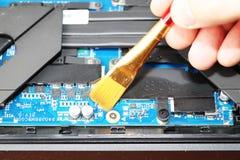 Ein Aussenseiter säubert eine Laptopkühlvorrichtung Verseuchtes Kühlsystem des Computers stockfoto