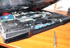 Ein Aussenseiter säubert eine Laptopkühlvorrichtung Verseuchtes Kühlsystem des Computers stockbild