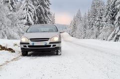 Ein Auto auf einer schneebedeckten Gebirgsstraße Lizenzfreies Stockbild