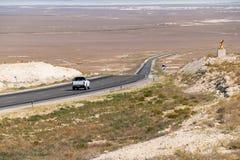 Ein Auto auf einer sonnigen Straße mitten in den Hügeln Stockbilder