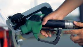 Ein Auto erhält mit der Anwendung einer Brennstoffpistole wieder getankt stock video footage