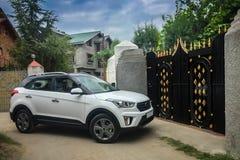 Ein Auto ungefähr, zum eines Hauses durch das Tor zu betreten, das im Augenblick geschlossen wird lizenzfreies stockfoto