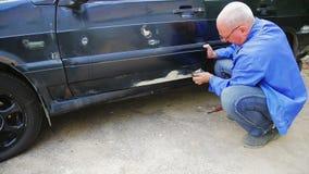 Ein Automechanikermann säubert Rost-feste Sitze auf einer Fahrzeugkarosserie