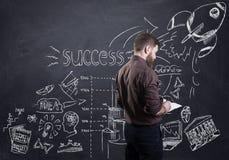 Ein bärtiger Geschäftsmann, der seinen Unternehmensplan gezeichnet auf schwarzes Brett darstellt lizenzfreie stockfotos