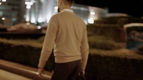 Ein bärtiger Geschäftsmann in einer beige Jacke mit einer Tasche in seiner Hand geht durch die Nachtstadt stock footage