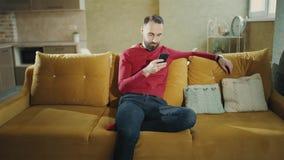Ein bärtiger Mann benutzt Handy und macht ein Abkommen, das zu Hause sitzt, freiberuflich tätig Gesamtlänge 4k stock video