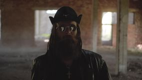 Ein bärtiger Mann in einem schwarzen Regenmantel und in einem Hut ist eine verlassene Fabrik Blicke mögen ihn ist, jagend oder  stock footage