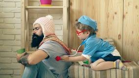 Ein bärtiger Mann an einer Aufnahme in einem kleinen Doktor Ein kleiner Junge in einer Doktor ` s Klage behandelt einen bärtigen  stock video footage