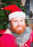 Ein bärtiger Mann in einer roten Klage von Santa Claus-Lächeln Lizenzfreie Stockbilder